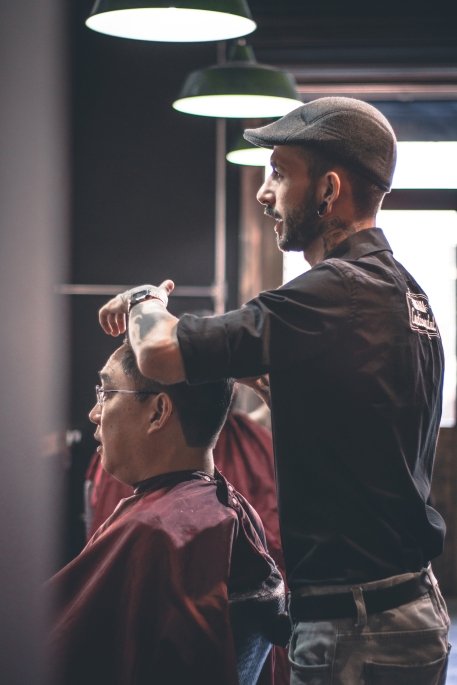 The right staff cutting hair of the customer.